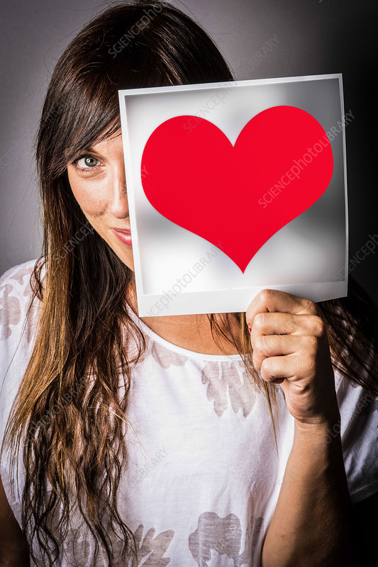 Woman holding heart picture in front of her face
