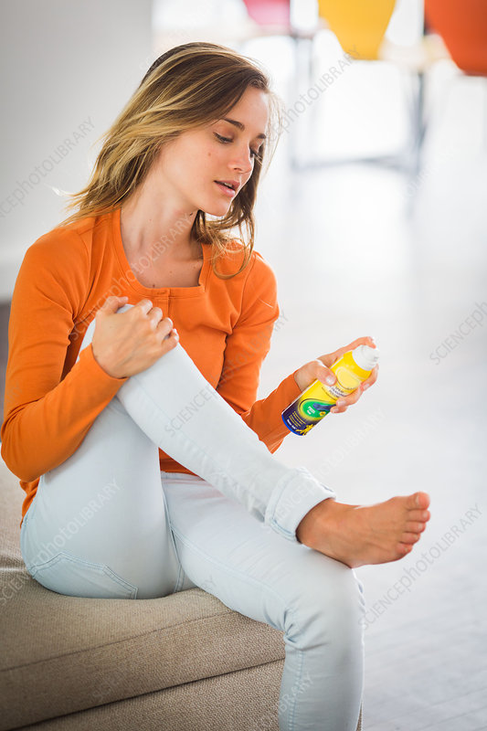 Woman applying foot care spray