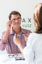Man trying on prescription glasses in opticians