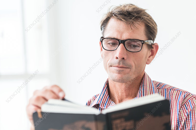 Man wearing glasses reading a book