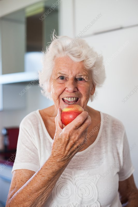 Elderly woman eating an apple