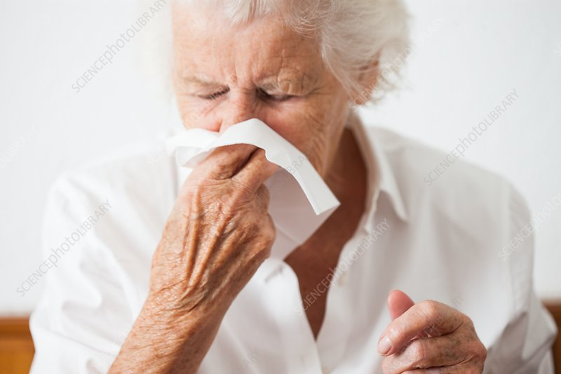 Elderly woman blowing her nose