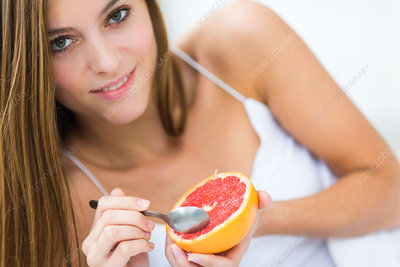 Woman eating a grapefruit