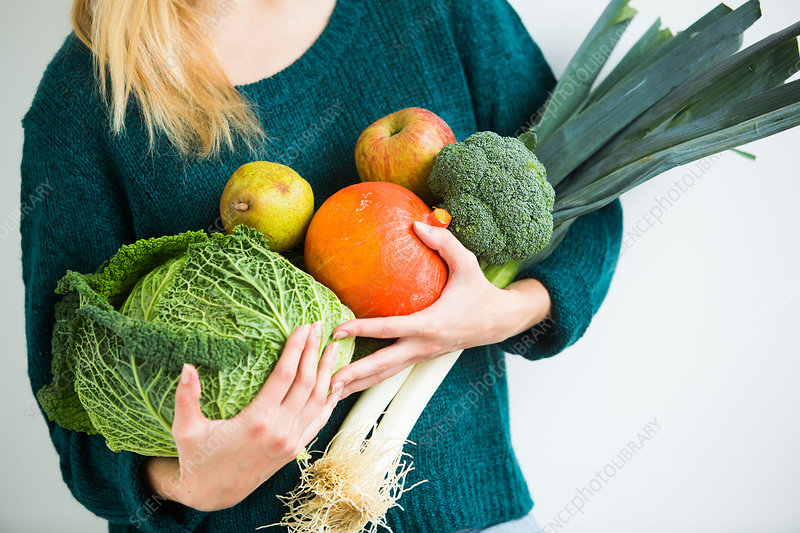 Woman holding fruits and vegetables in her arms