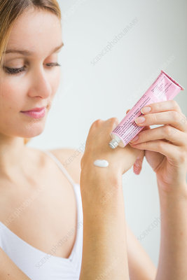 Woman applying moisturizing cream on her hands