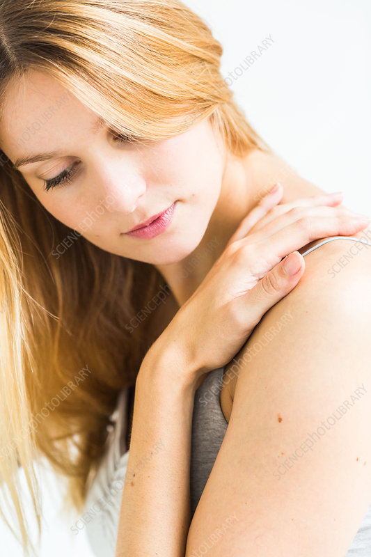 Shoulder pain, Woman rubbing her shoulder