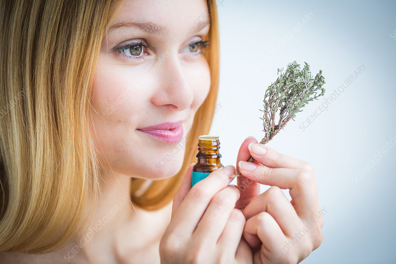 Woman smelling a bottle of thyme essential oil