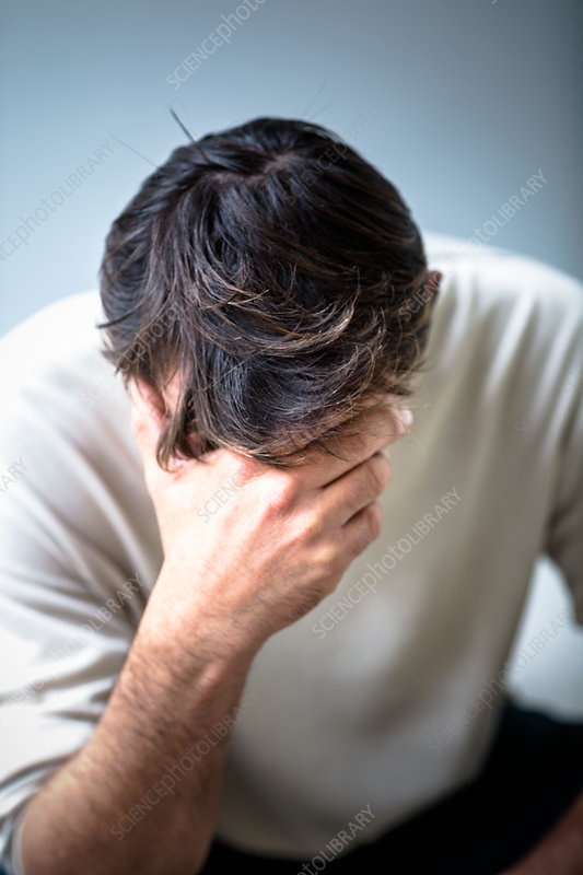 Depressed man holding his head in his hands