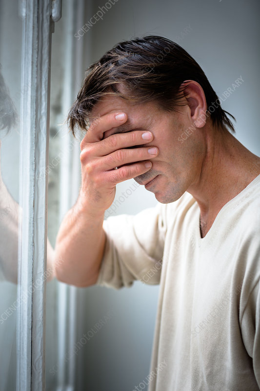 Depressed man holding his head in his hand