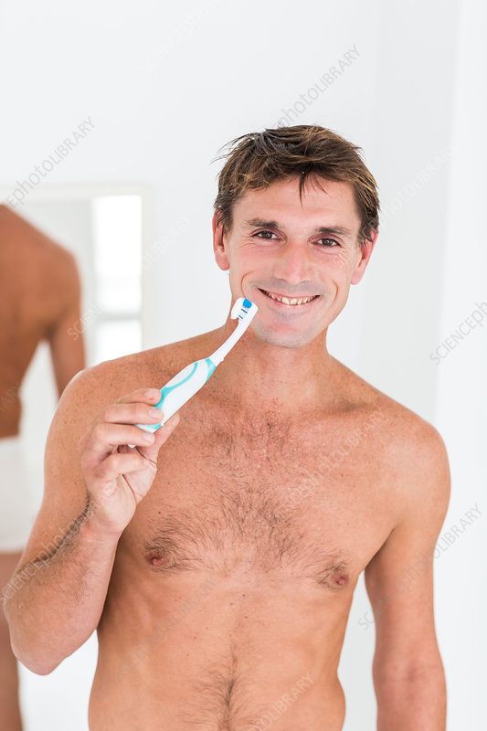 Man brushing her teeth with electric toothbrush
