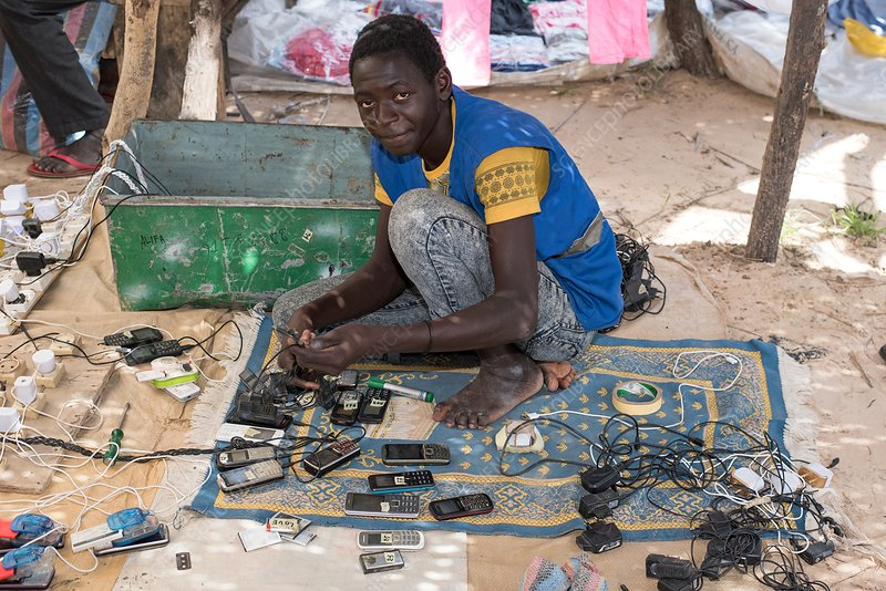 Cell phone repairman in a market in Chad