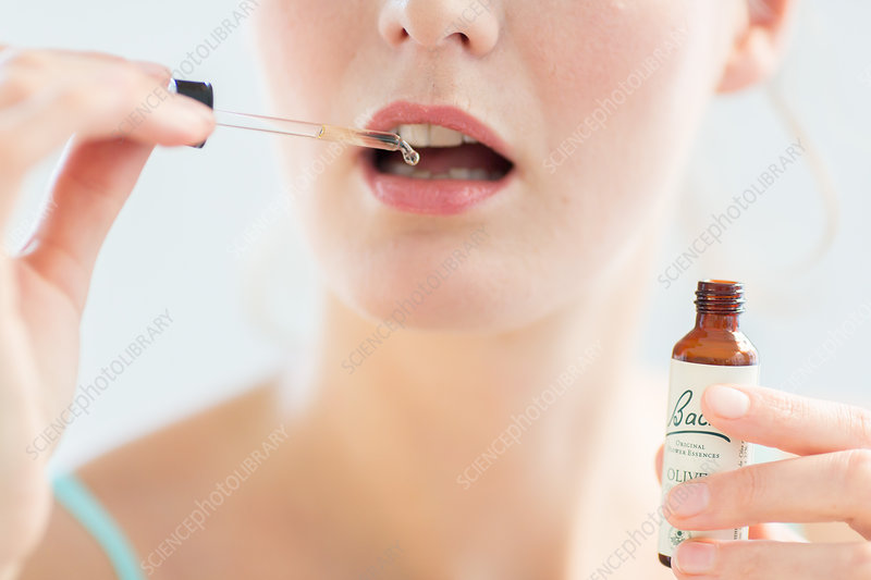Woman using a Bach remedy (liquid flower extract)