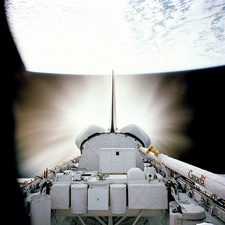 Space shuttle engines firing in orbit