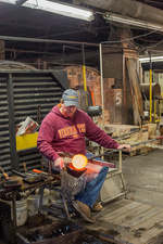 Glassblower shaping a molten glass vessel