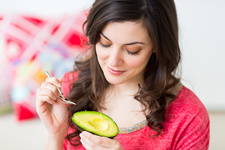 Woman eating an avocado