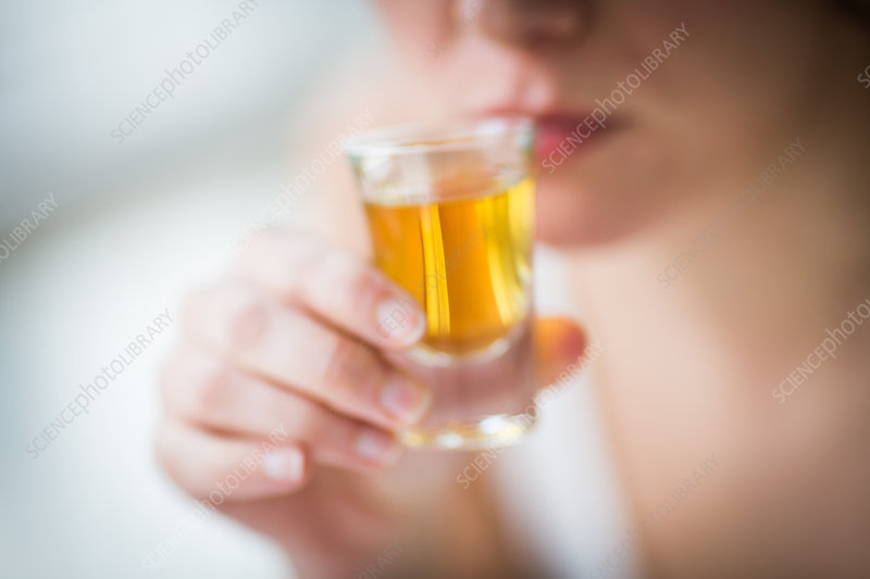Woman drinking an alcohol shot