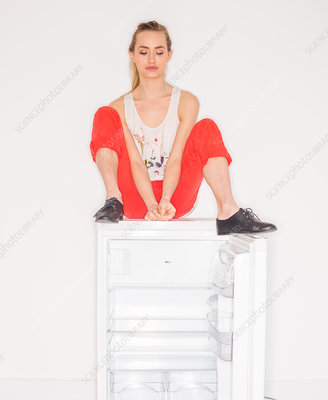 Woman sitting on a fridge