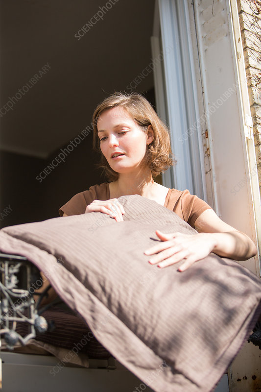 Woman beating pillows at the window