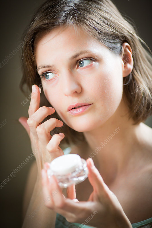 Woman applying moisturizing cream
