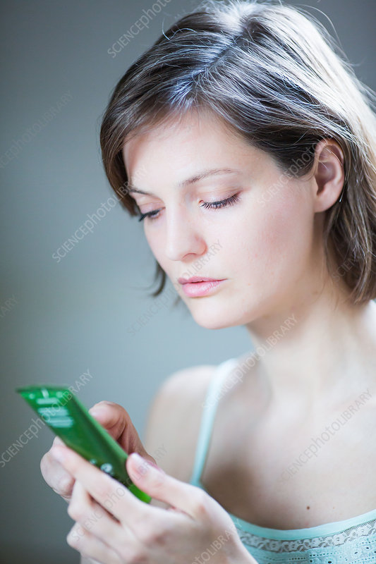 Woman reading composition of cosmetic product