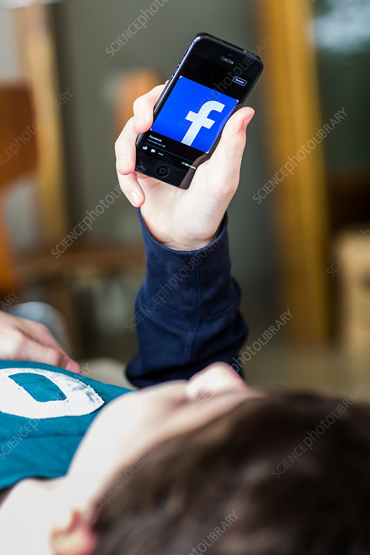 Teenage boy using Facebook on a Smartphone