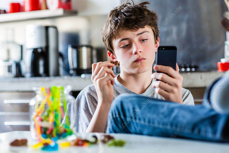 Teenage boy eating sweets