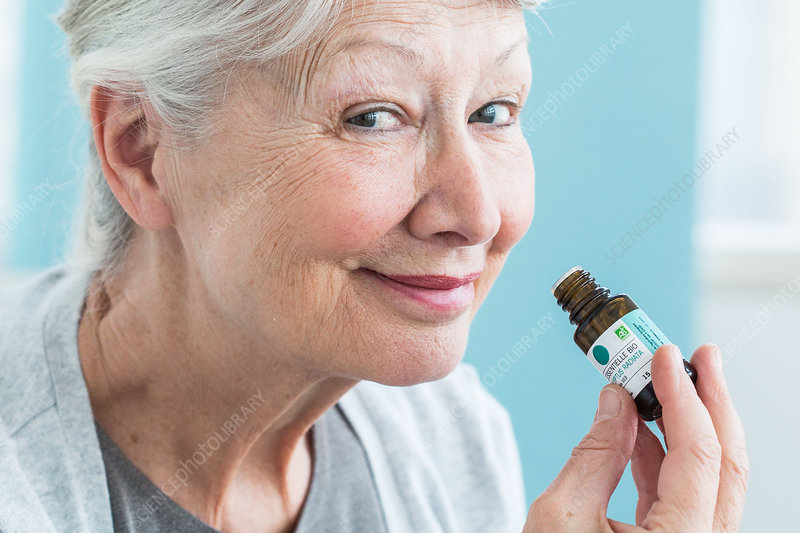 Woman smelling a bottle of essential oil