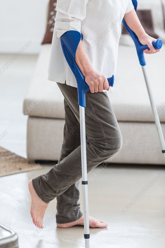 Elderly woman walking with crutches