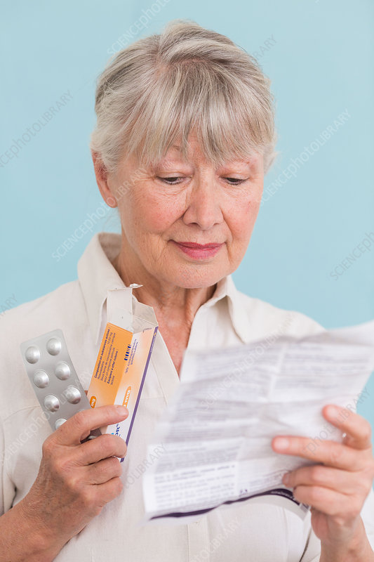Woman reading medicine instruction sheet
