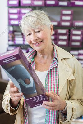 Woman choosing a knee support in a pharmacy