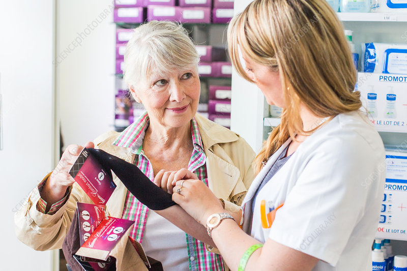 Pharmacist showing a customer support stockings
