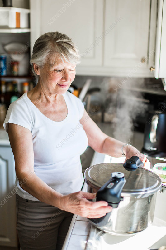 Senior woman using a pressure cooker