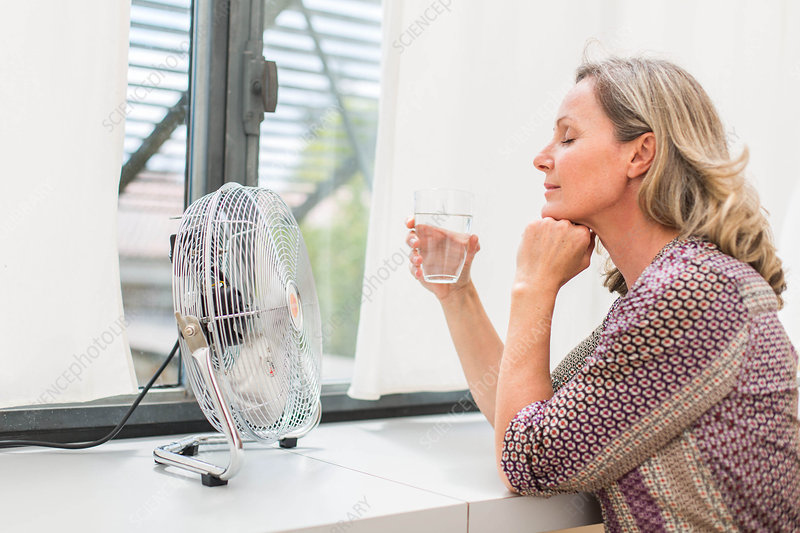 Woman using an electric fan