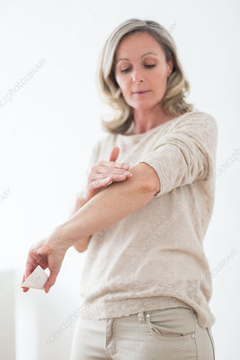 Woman applying cream on her elbow