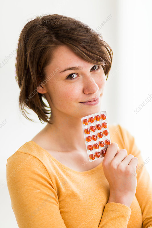 Woman taking food supplement capsules