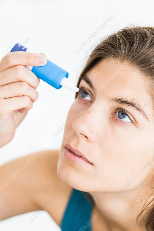 Woman applying eye-drops into her eye