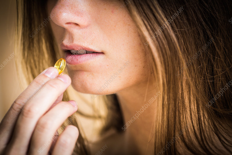 Woman taking food supplement capsule