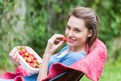 Young woman eating strawberries