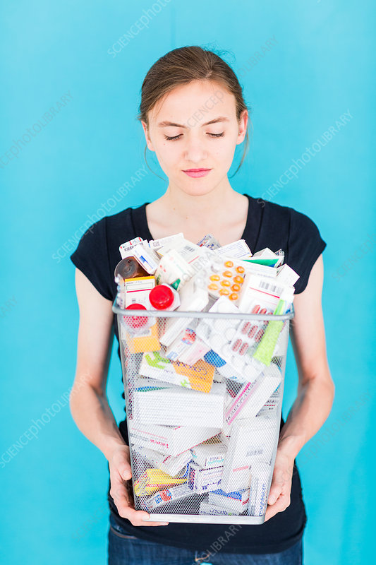 Woman placing pill packaging in a dustbin