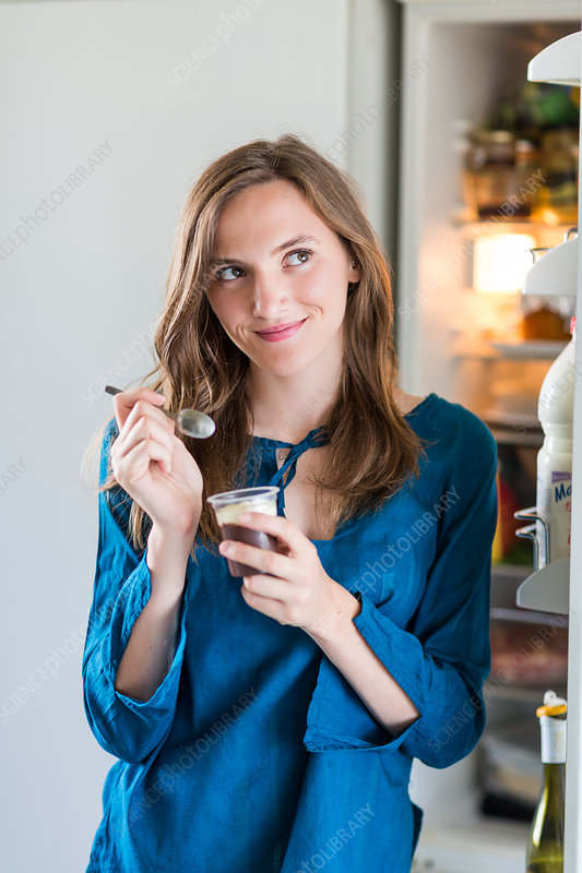 Woman eating yoghurt with chocolate