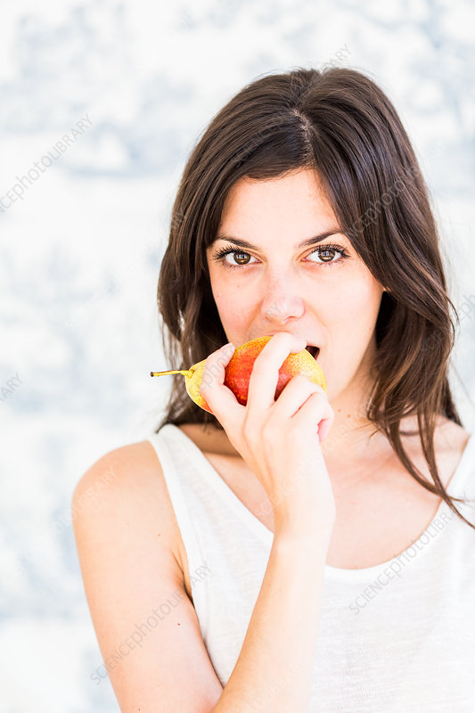 Woman eating a pear