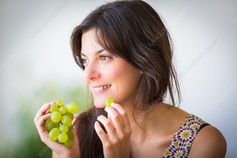 Woman eating grape