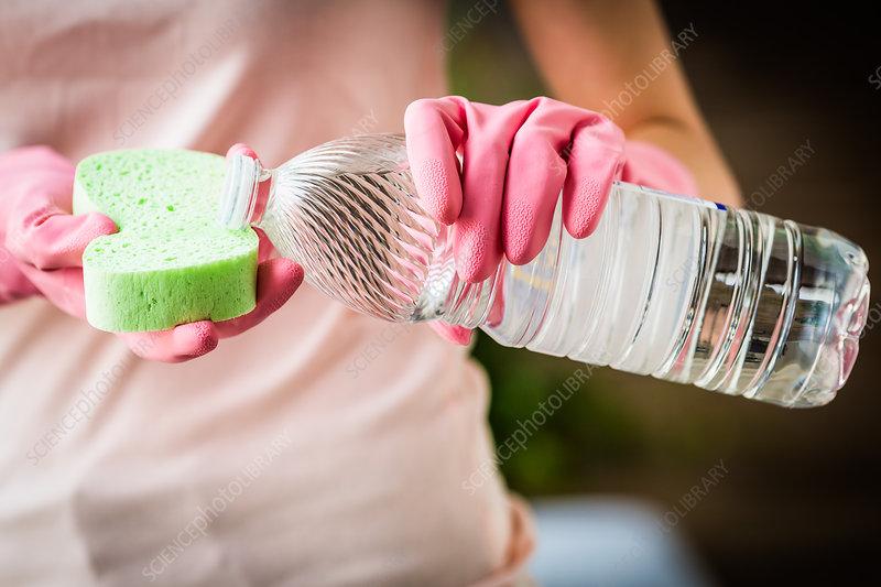 Woman using white vinegar to clean