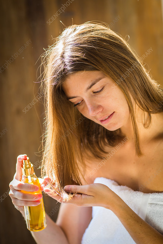 Woman applying oil on the tip of the hair
