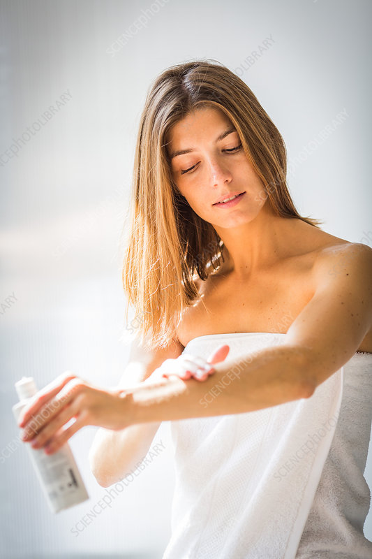 Woman applying cream on her arm