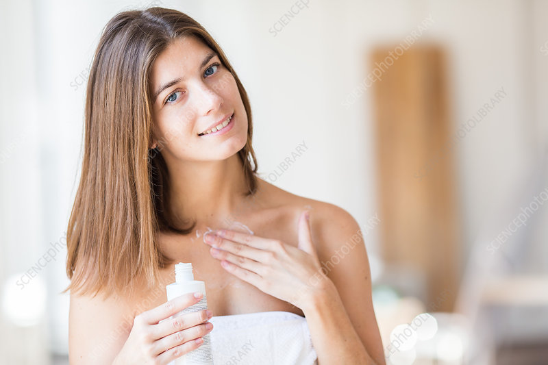 Woman applying cream on her low neckline