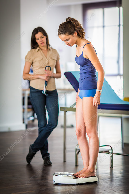 Doctor weighing a patient