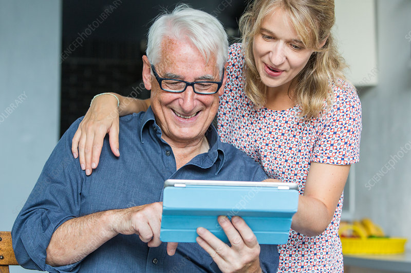 Woman helping senior to use a digital tablet