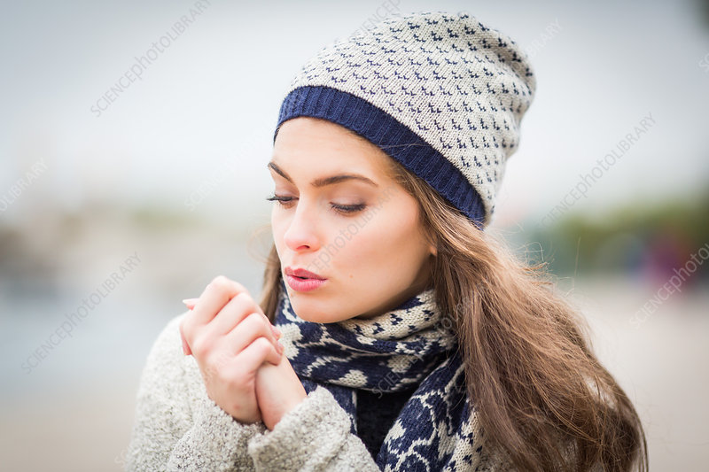 Woman blowing on her hands