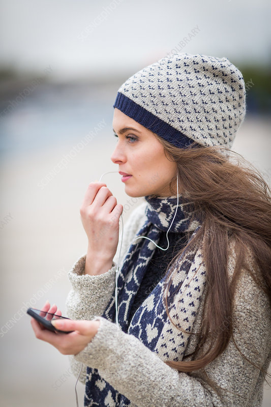Woman using her cell phone with a hands-free kit